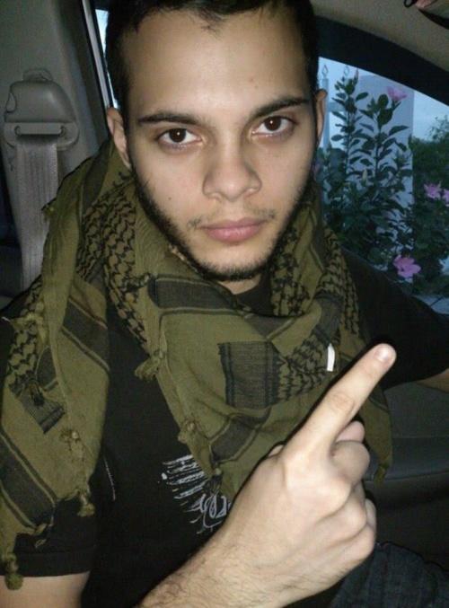 """Esteban Santiago da han var i militæret. Her ses han gøre """"en-finger"""" tegnet, ISIS varemærke."""